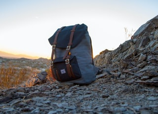 gray and black backpack on top of cliff