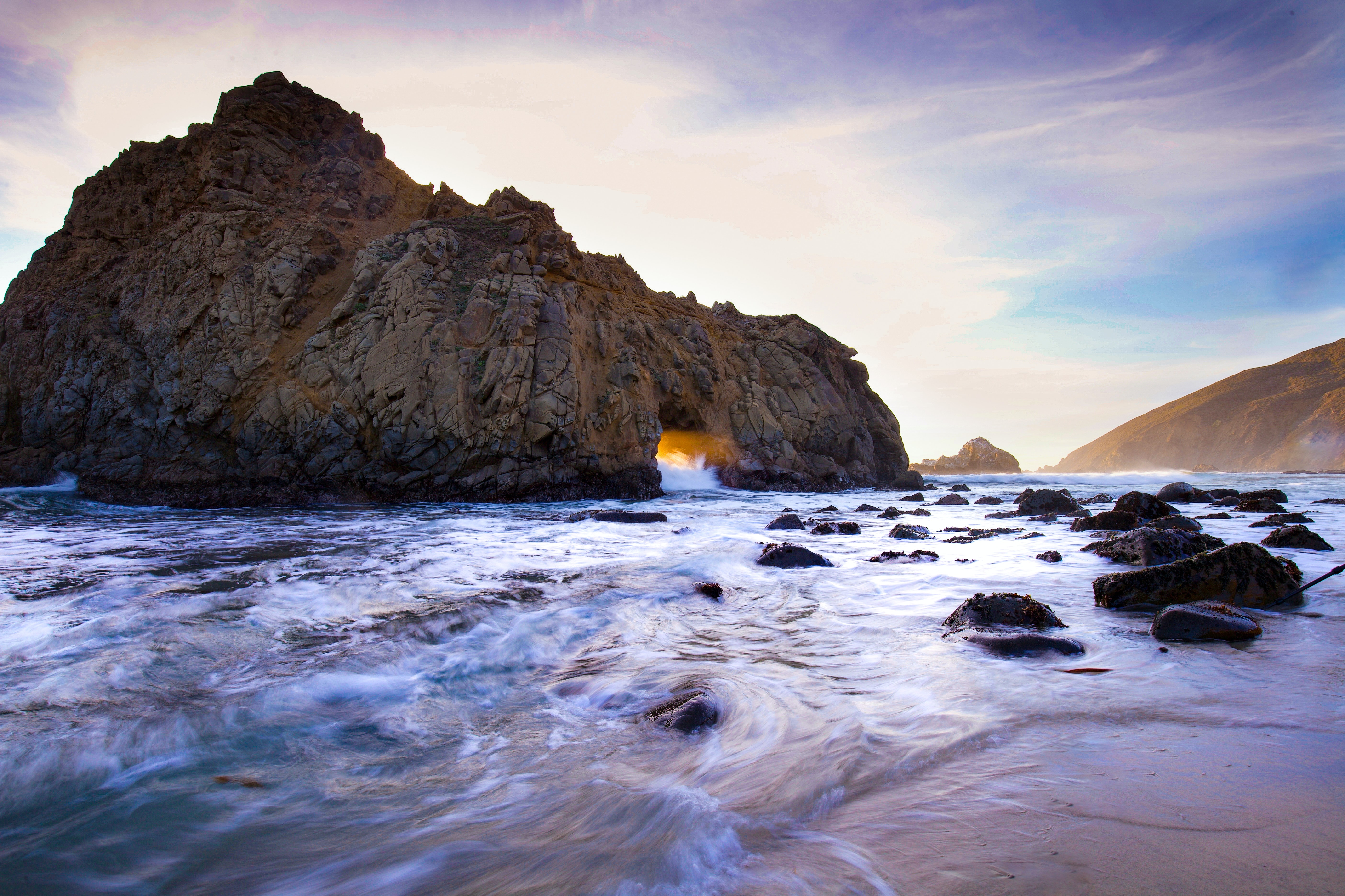 time lapse photography of body of water near rock formation