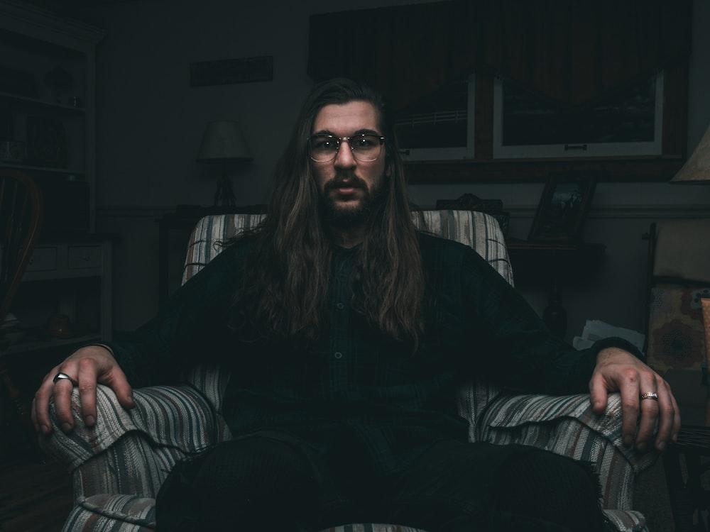 man in black dress shirt sitting on sofa chair