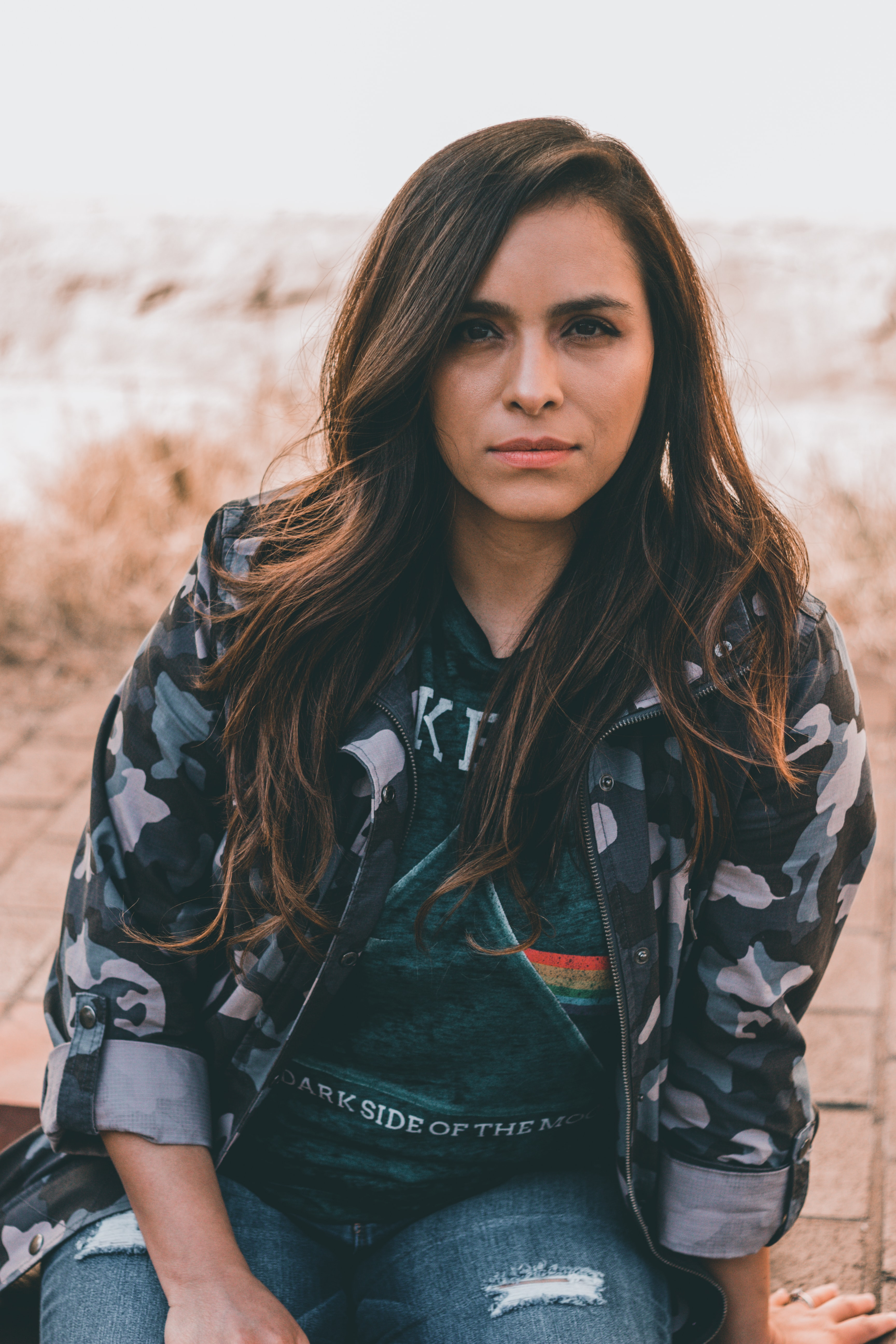 women's black, white, and green camouflage zip-up jacket sitting on concrete floor