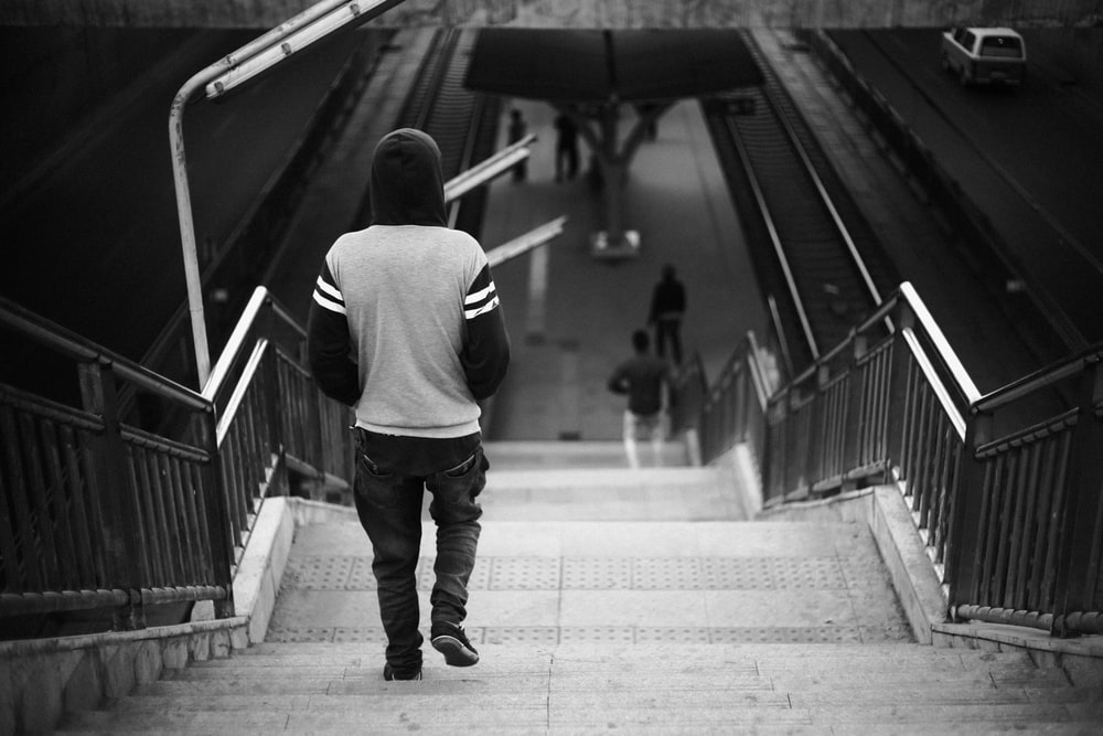 grayscale photo of person wearing hoodie walking on stairs
