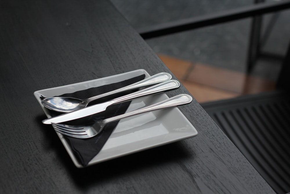 stainless steel spoon and fork on black ceramic plate