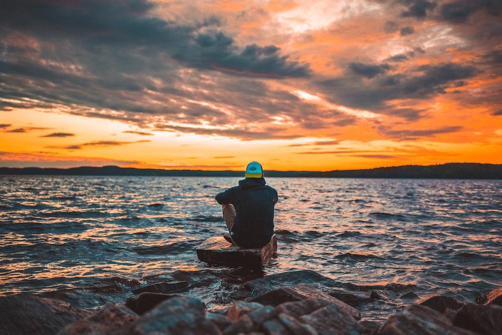 man sitting on gray rock during sunset