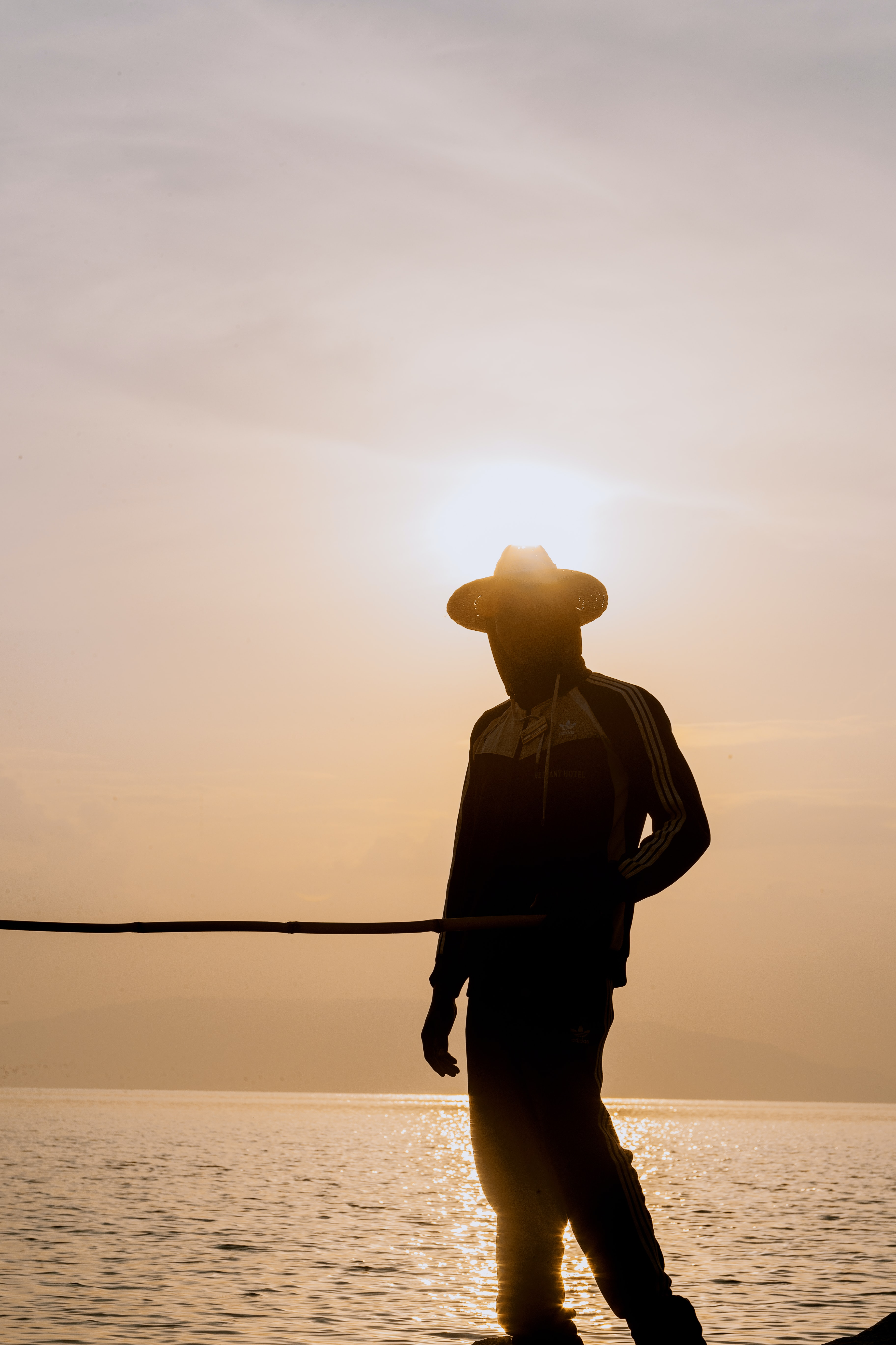silhouette photo of person wearing sun hat during sunset
