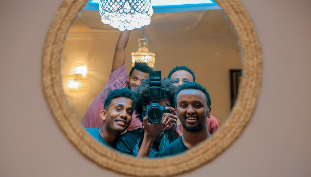 group of people taking mirror photo