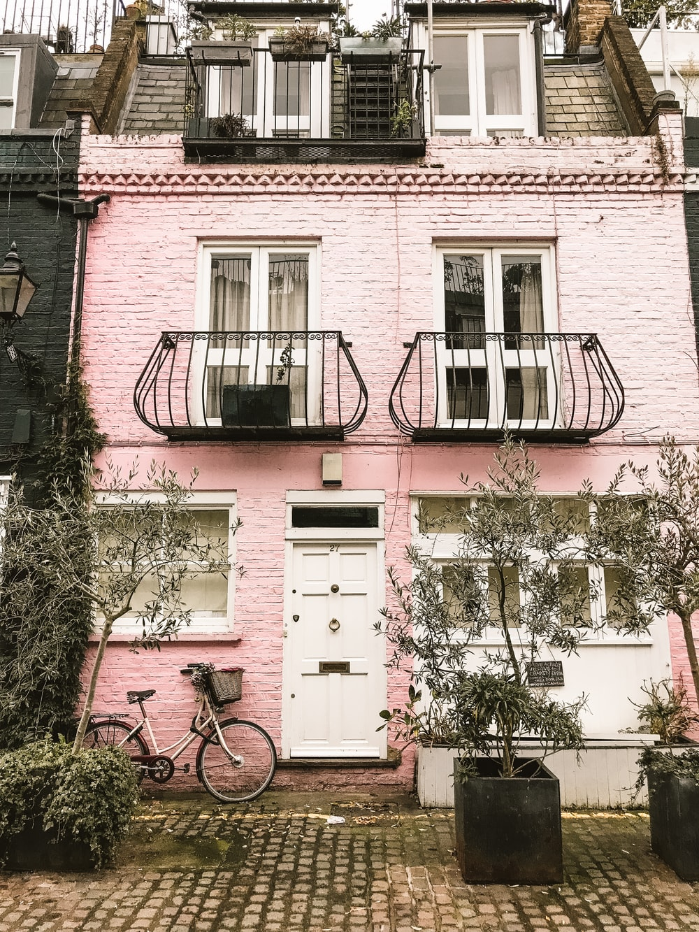 bicycle beside pink wall