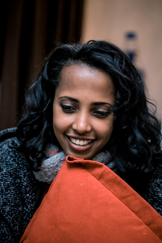 woman holding orange throw pillow