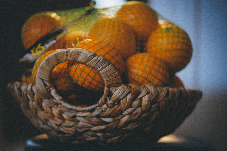 selective focus photo of bunch orange fruit in brown wicker basket
