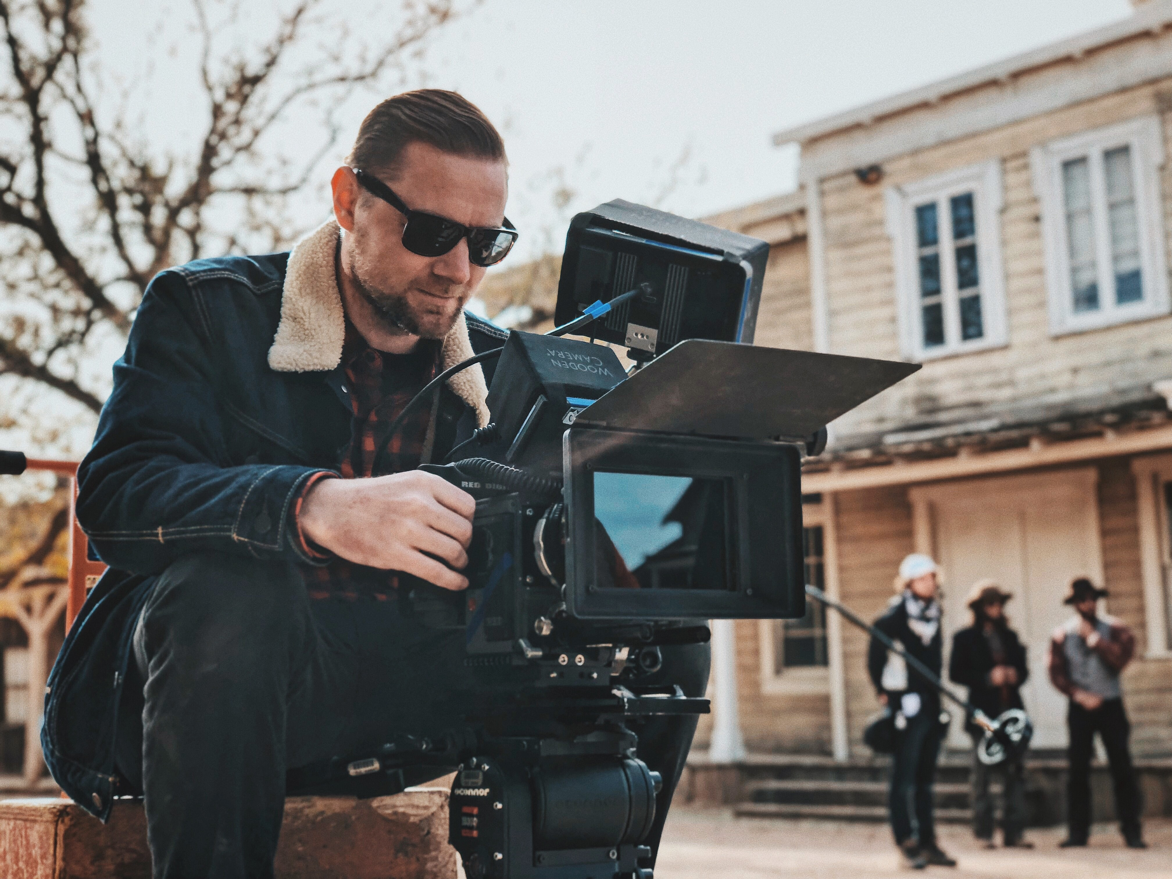 man sitting on bench near house while holding camera during daytime
