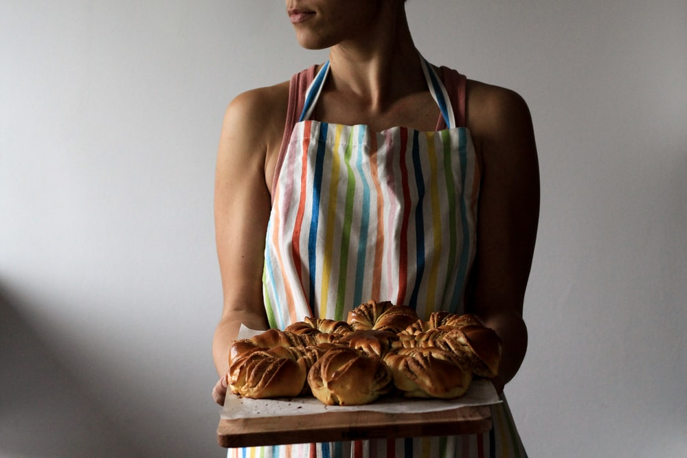 woman holding tray with breads