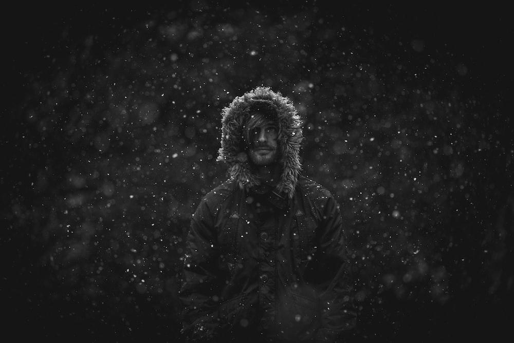 man wearing parka jacket in snow