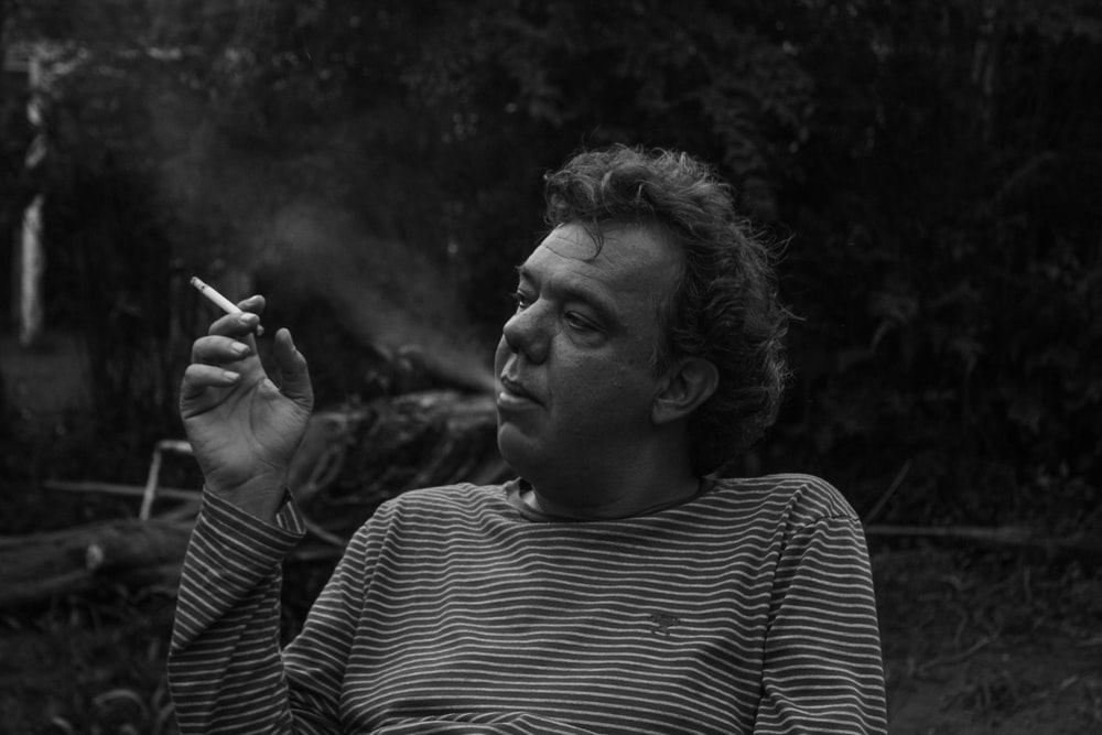 grayscale photography of man white smoking