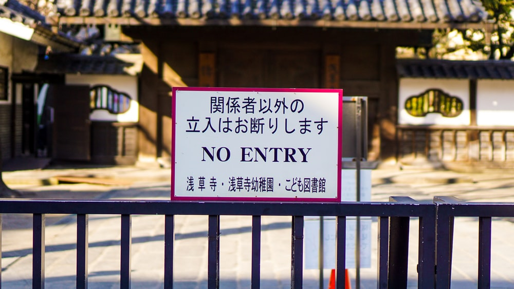 no entry sign on metal rail in front of building during day