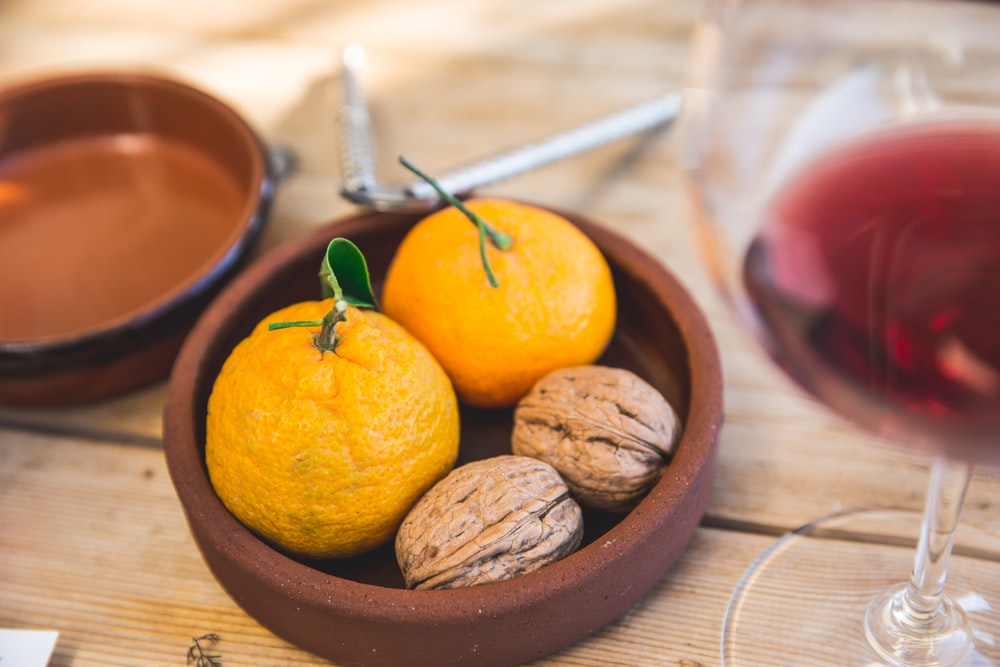 two oranges and two nuts on round brown clay bowl