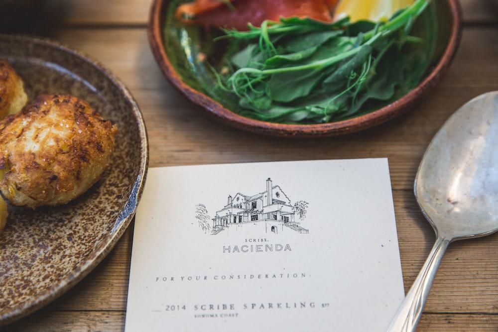 Hacienda book beside green vegetable on plate