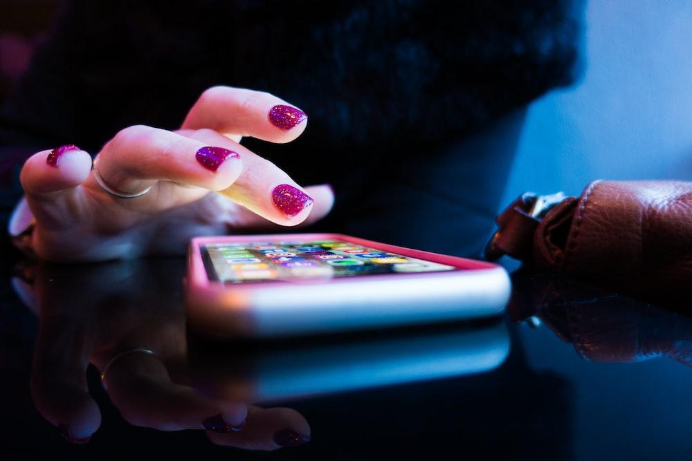 黑色的智能手机,灰色和粉红色的情况下使用的人
