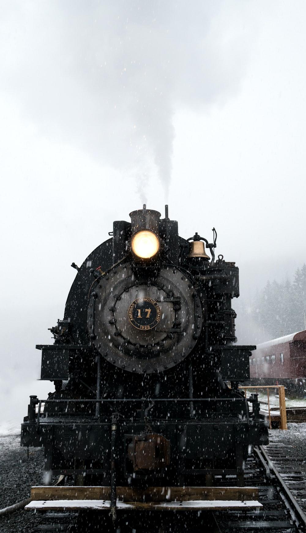 black train on railway at daytime