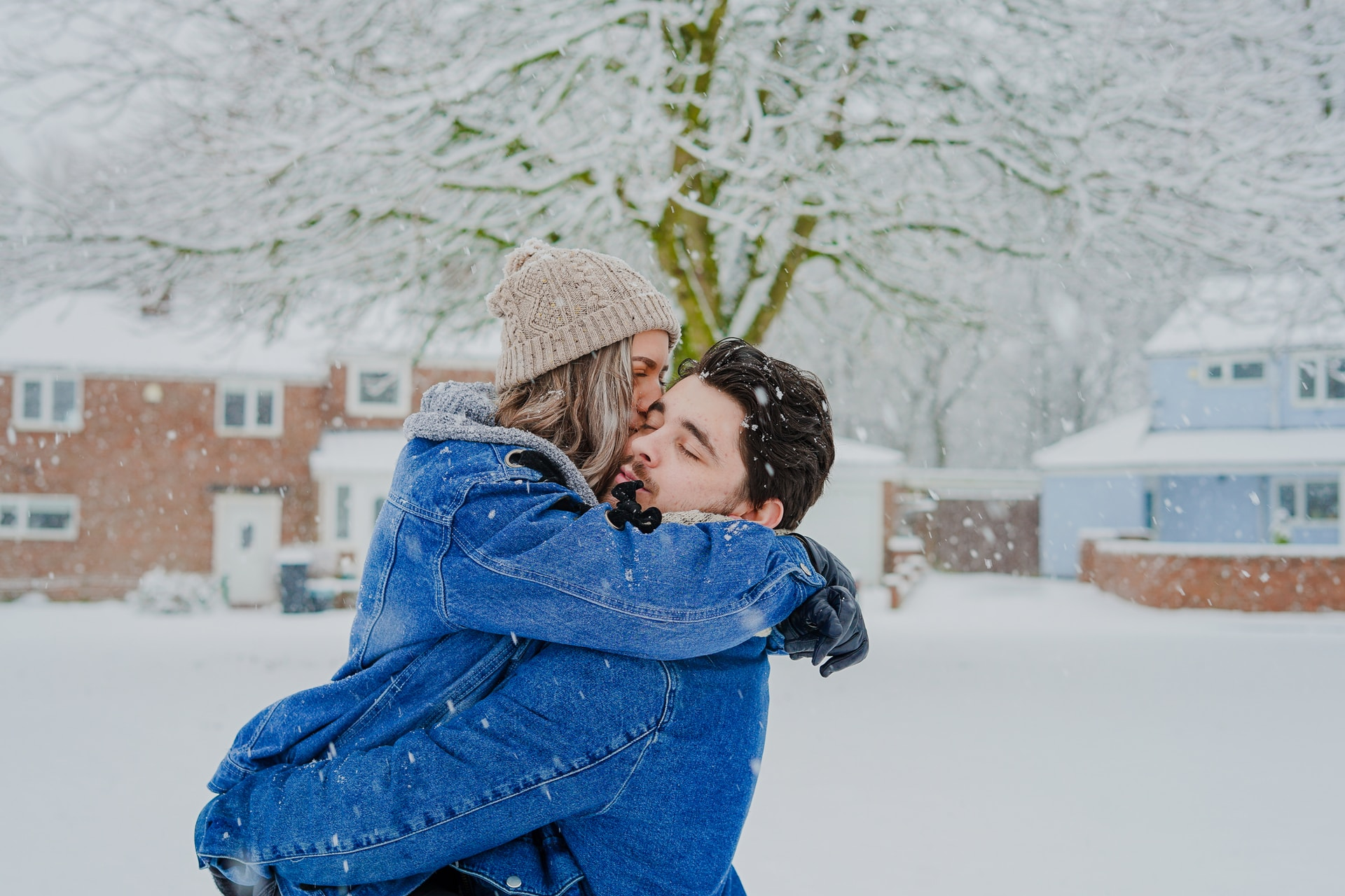 man and woman hugging on snow field