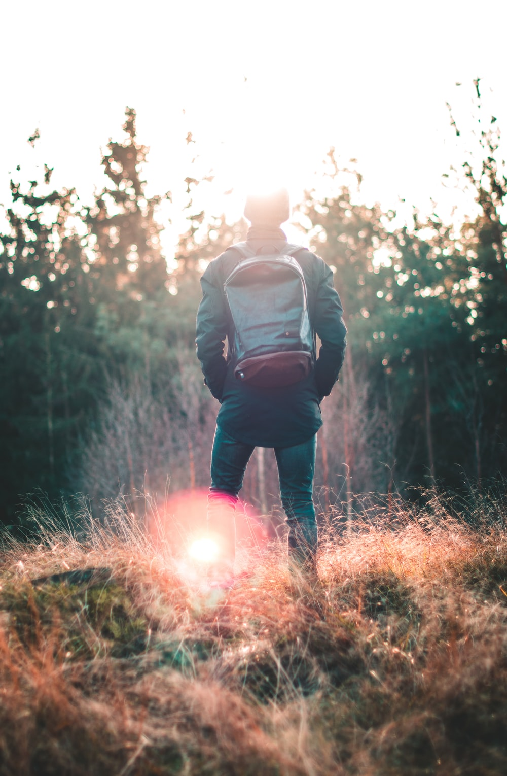 man wearing black backpack in shallow focus photography