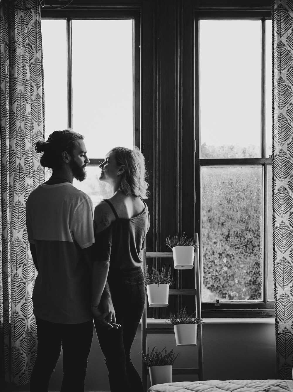 man and woman facing each other near window