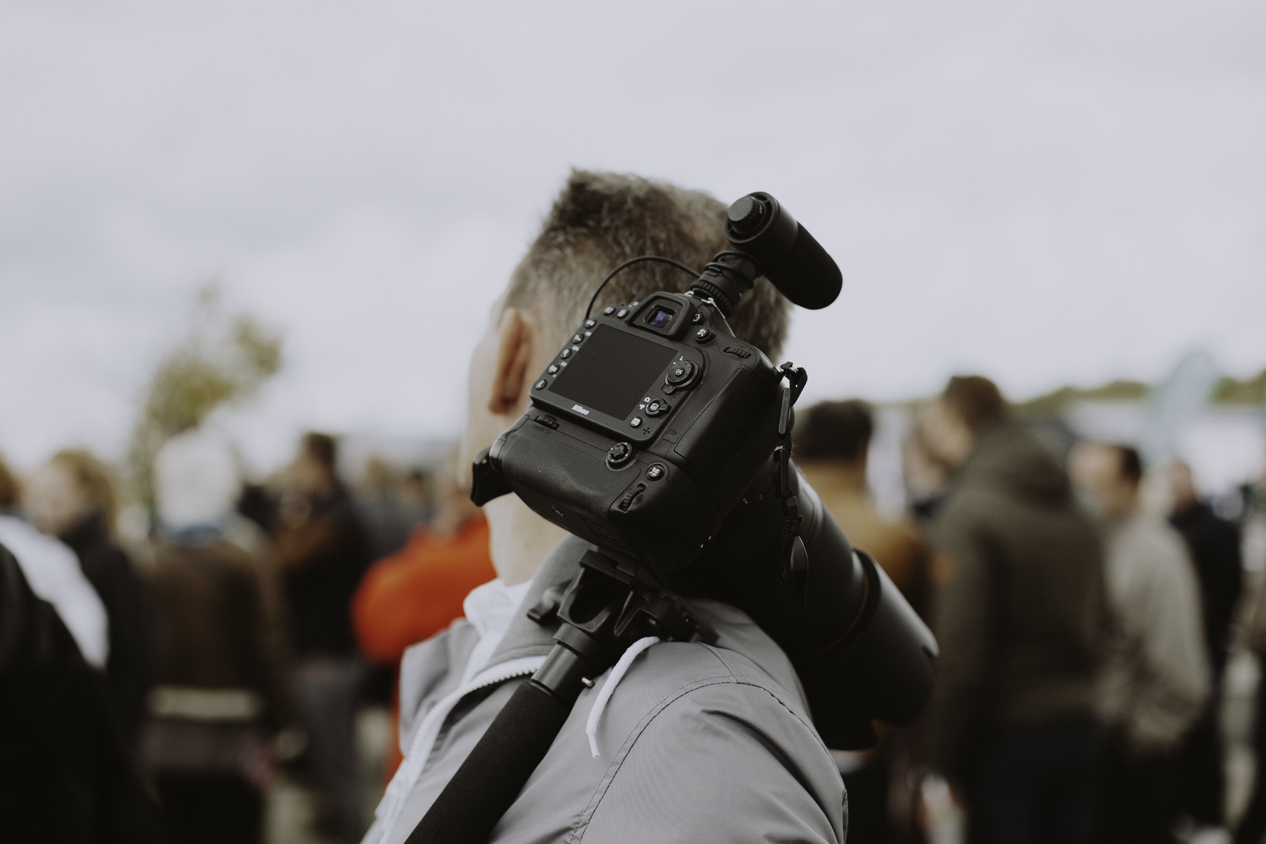 man with black DSLR camera on his shoulder