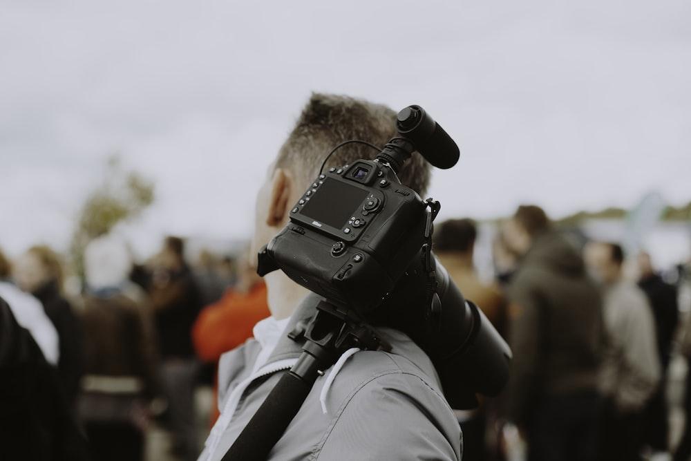 man with black DSLR camera on his shoulder