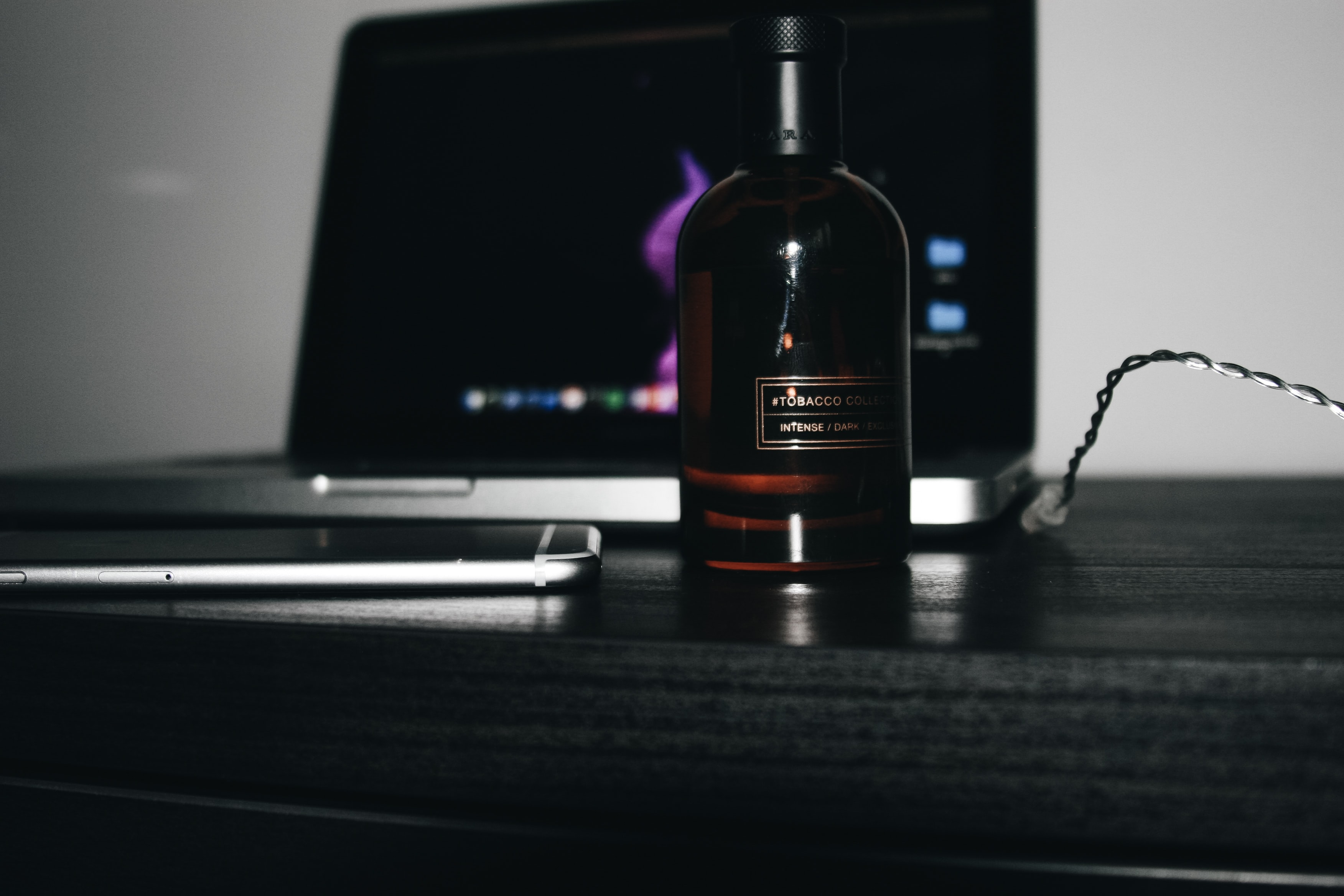 black glass bottle beside smartphone and laptop
