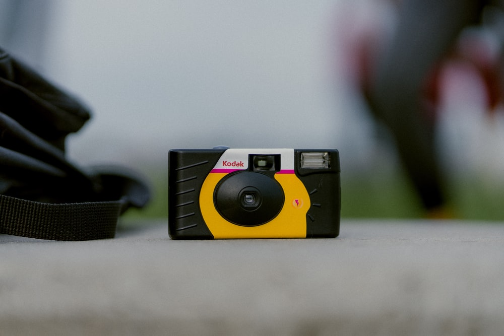 selective focus photograph of black and yellow Kodak camera