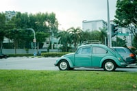 teal Volkswagen beetle parked on gray concrete road during daytime
