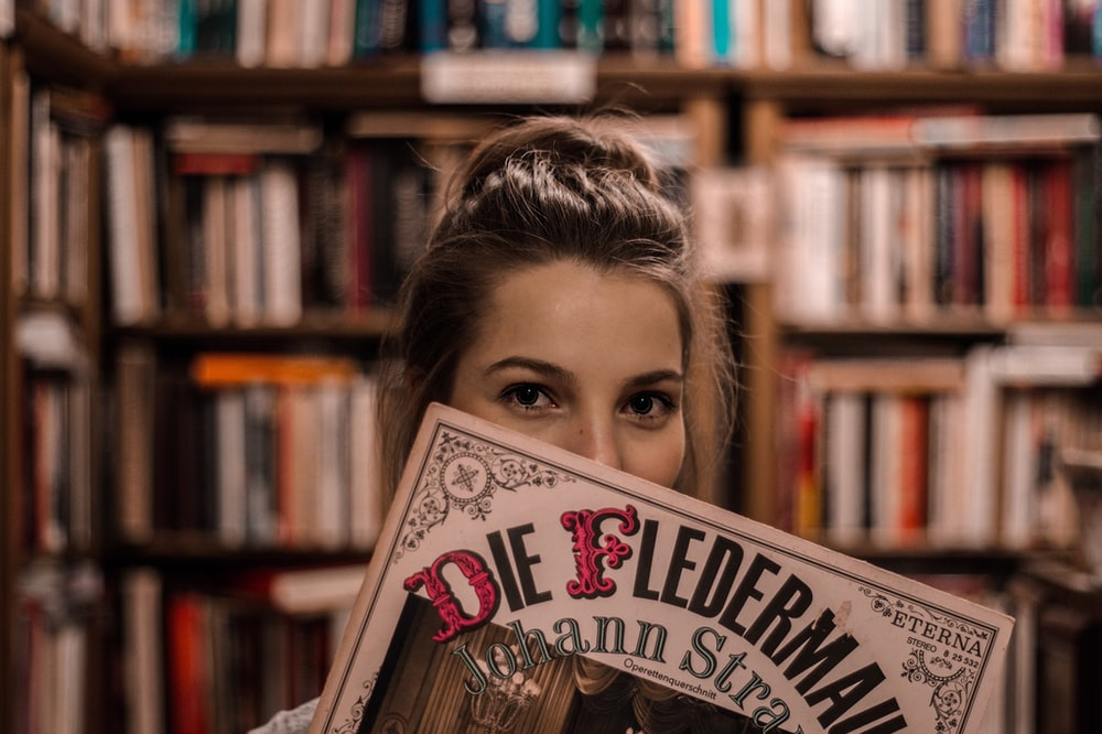 woman covered her face with book