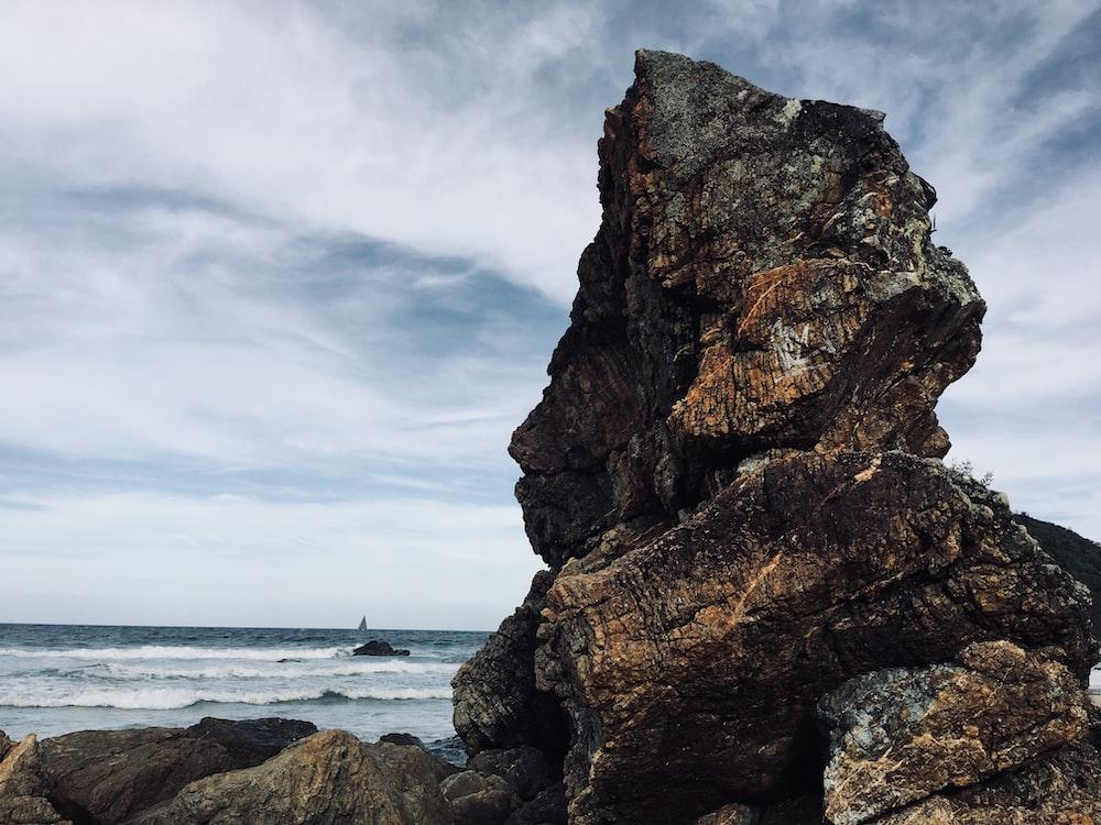 rocky mountain near sea at daytime
