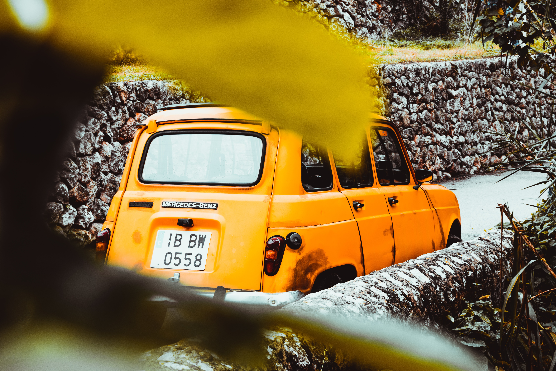 yellow car near stone wall at daytime