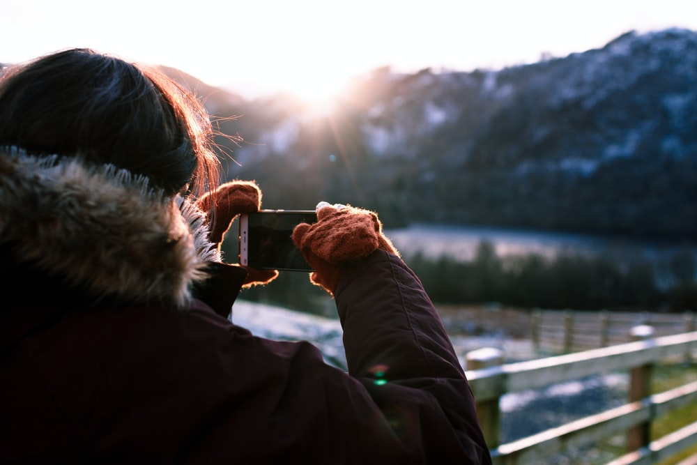 person wearing parka holding phone taking photo