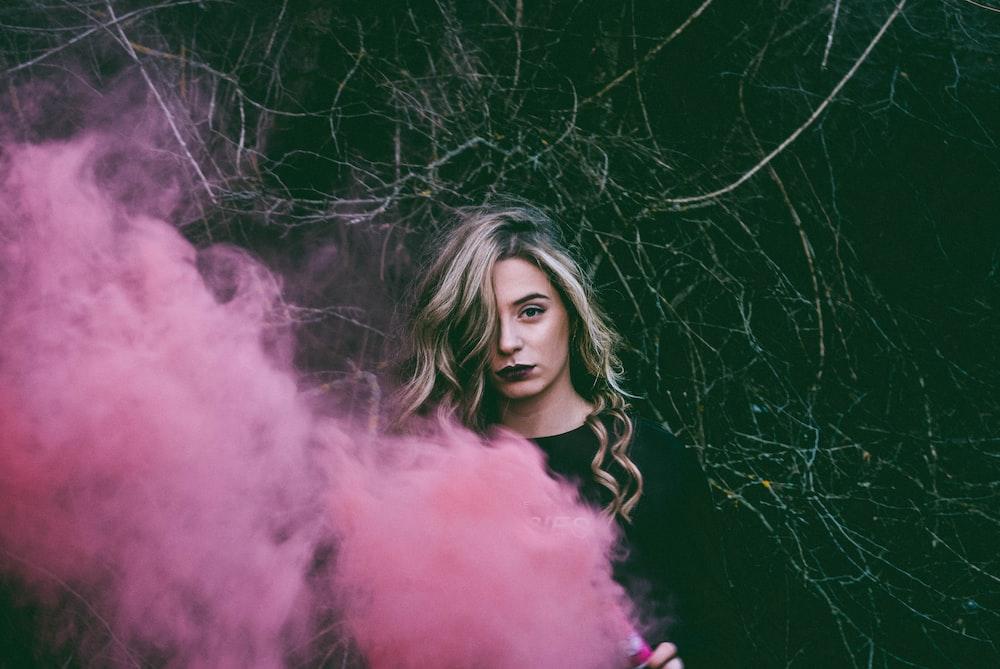 woman standing near pink smoke