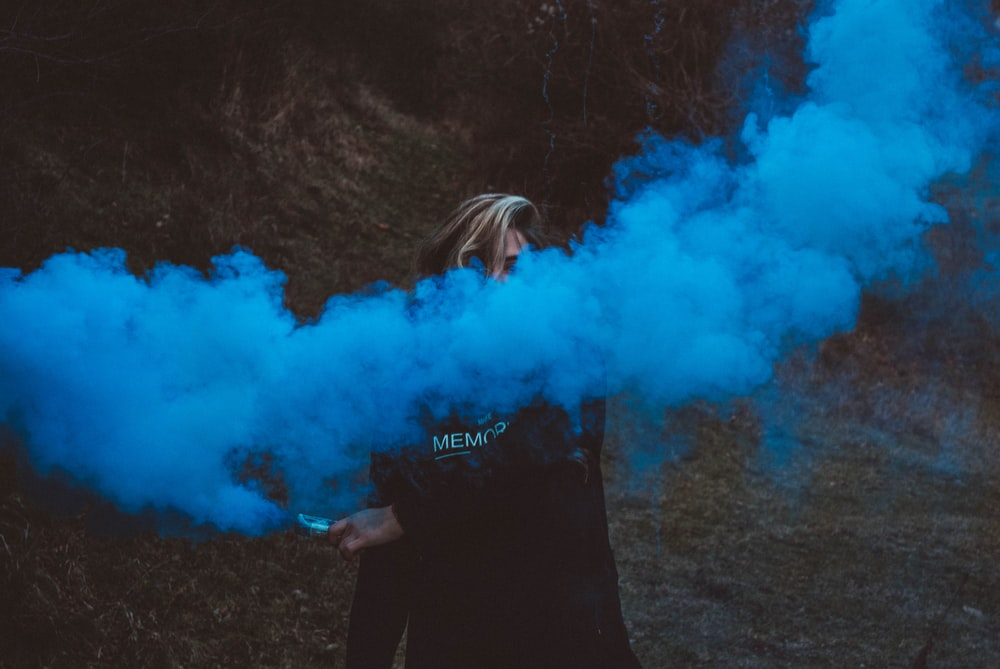 person holding blue smoke