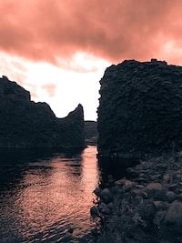 photo of body of water between cliff