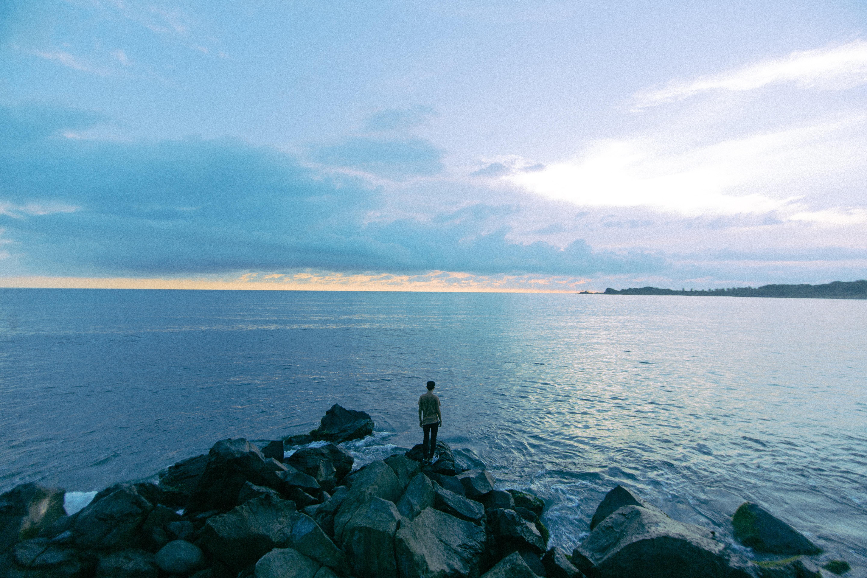 man standing on rock near seashore during daytime