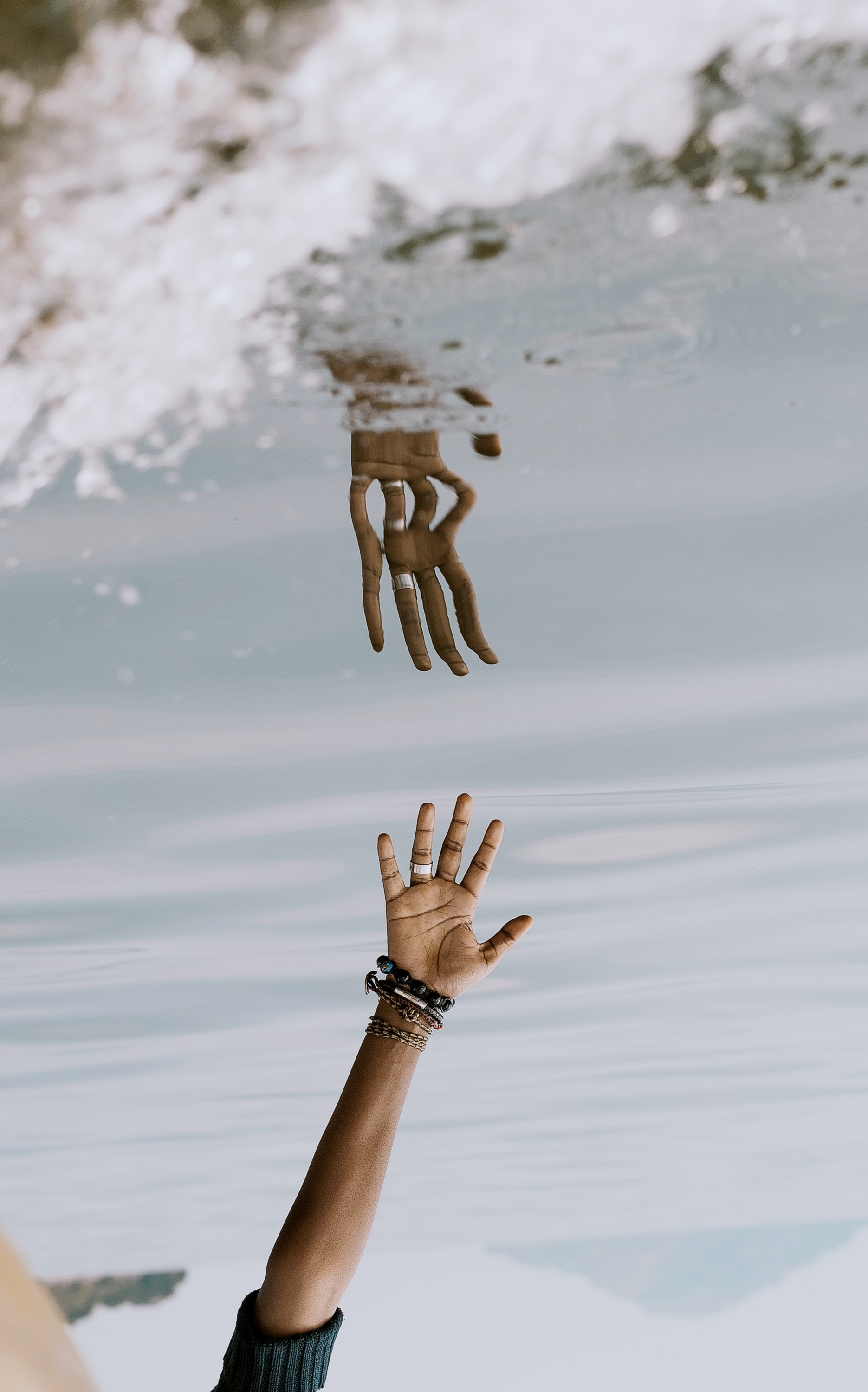 person's hand reaching on water with reflection ]