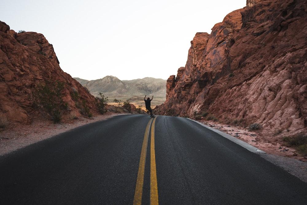 man skateboarding in the road