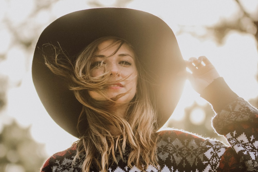 woman touching her hat during daytime in shallow focus photography