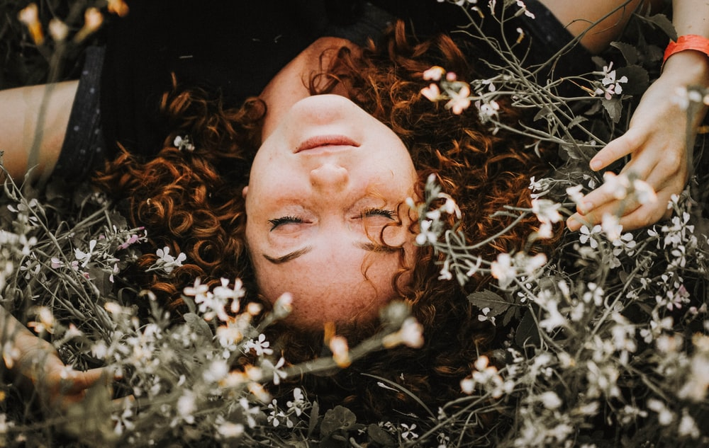 woman lying on flowers during daytime