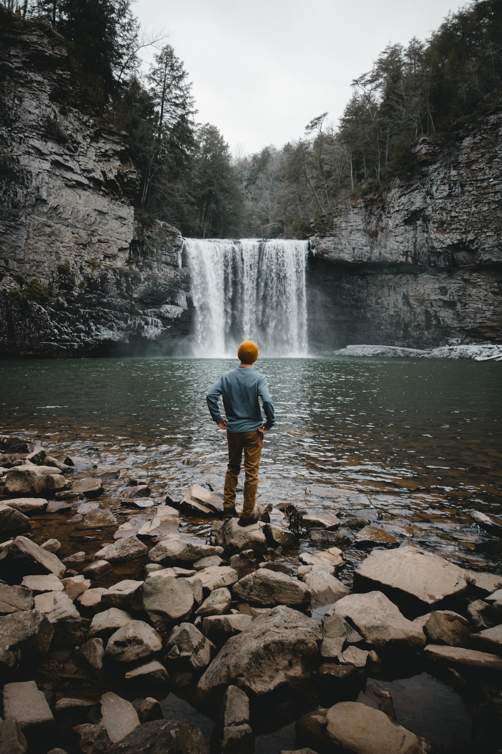 man standing on brown stone facing waterfalls