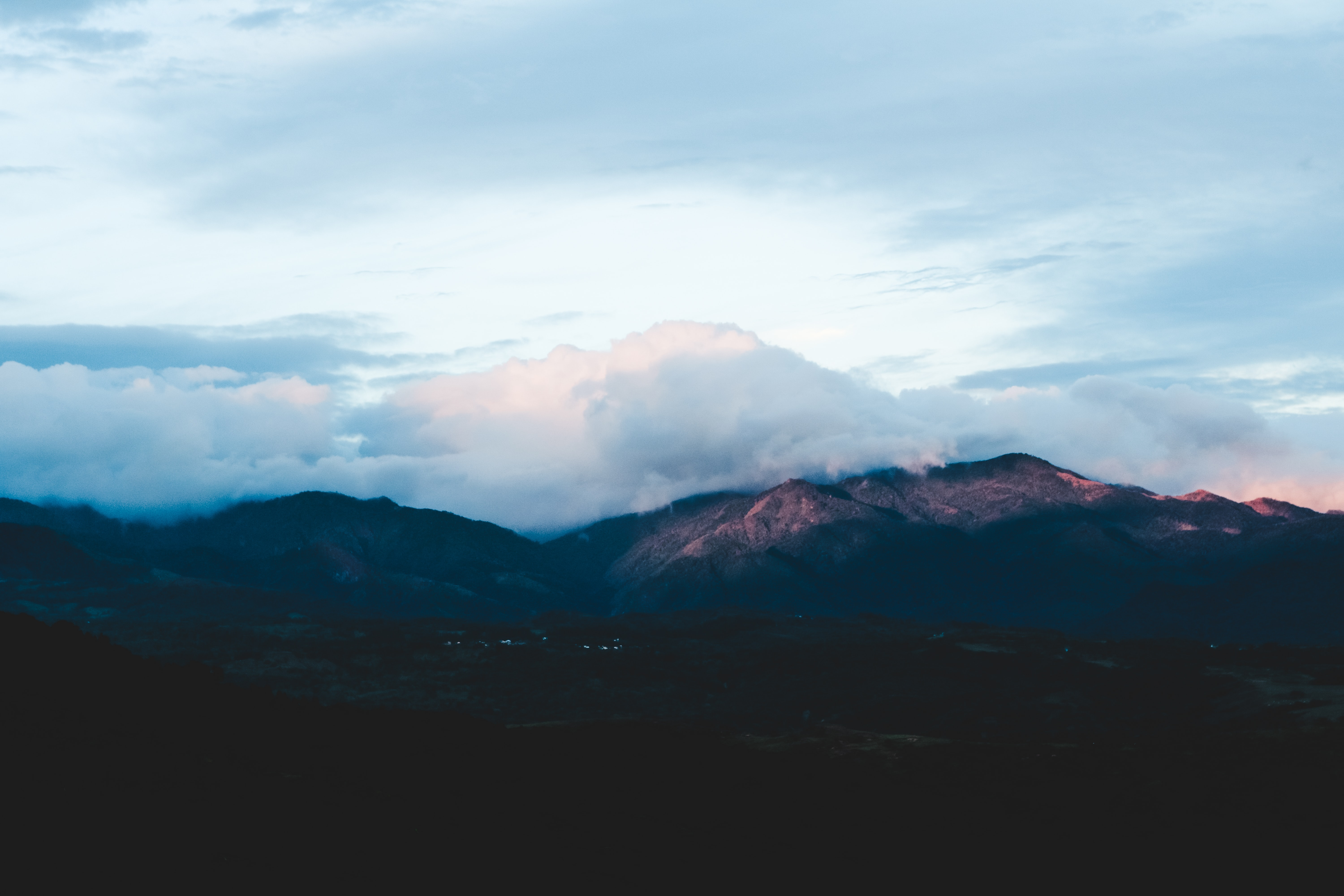 landscape photo of mountains under white clouds