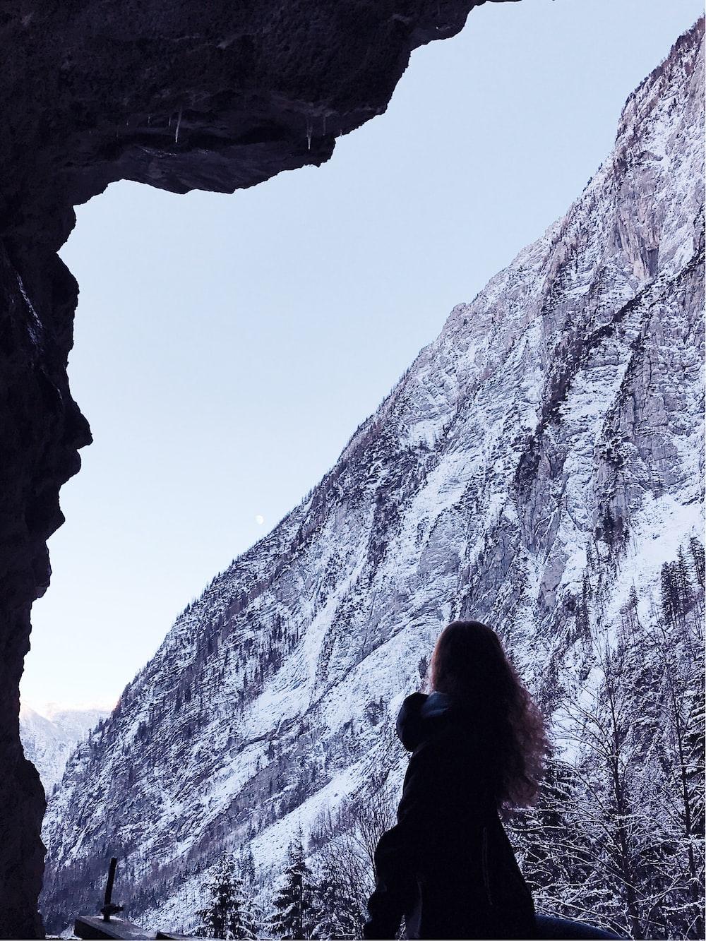 woman in black top standing near mountain