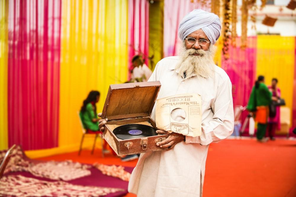 man in white thobe holding vinyl player