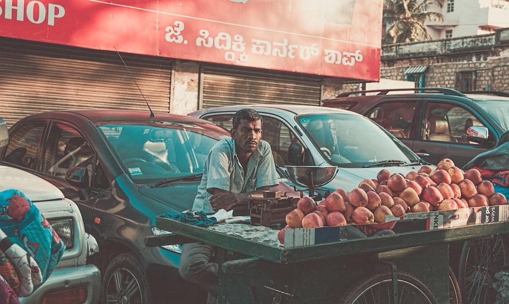 man vending apples near parked cars during daytime