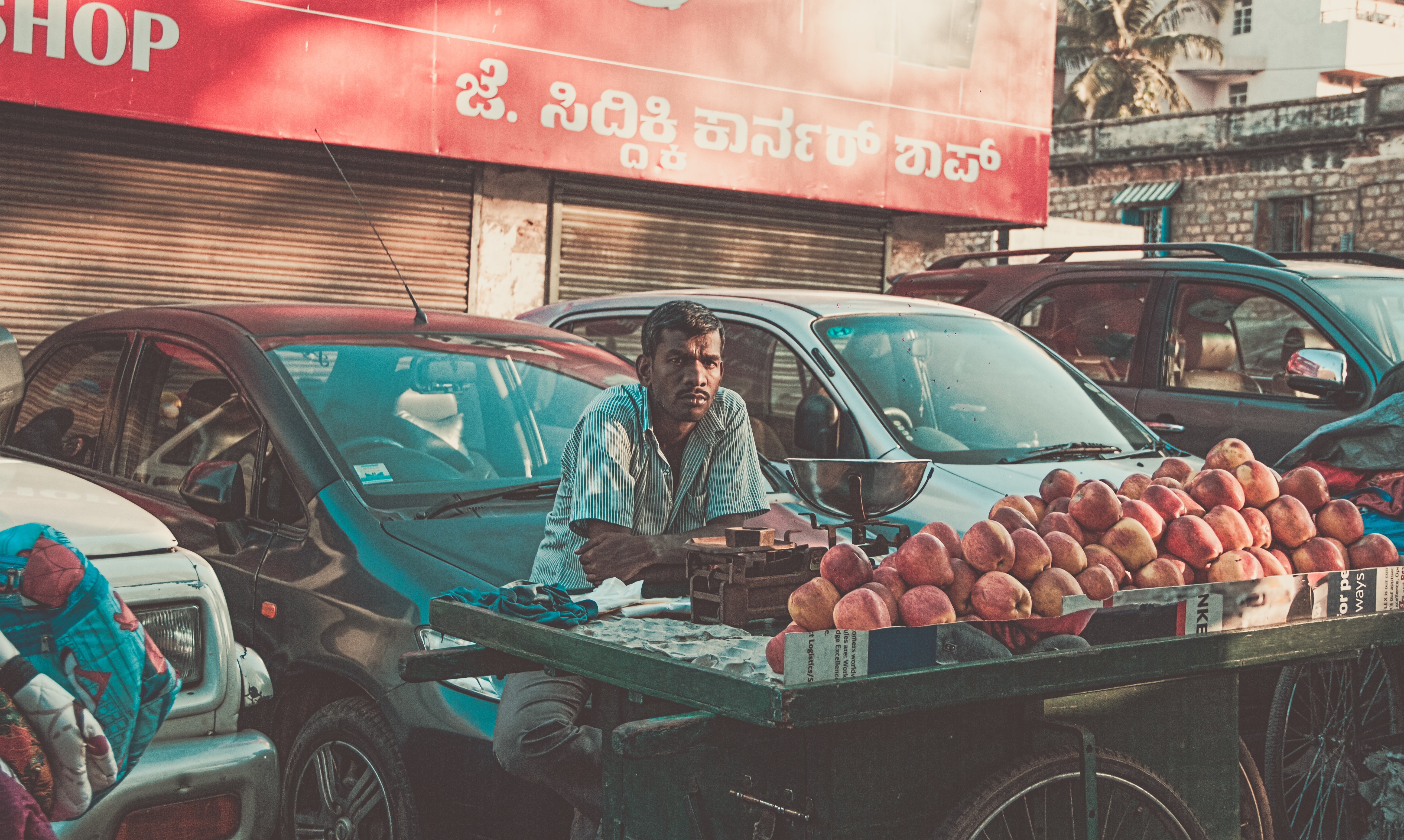 man vending apples near parked cars during daytime