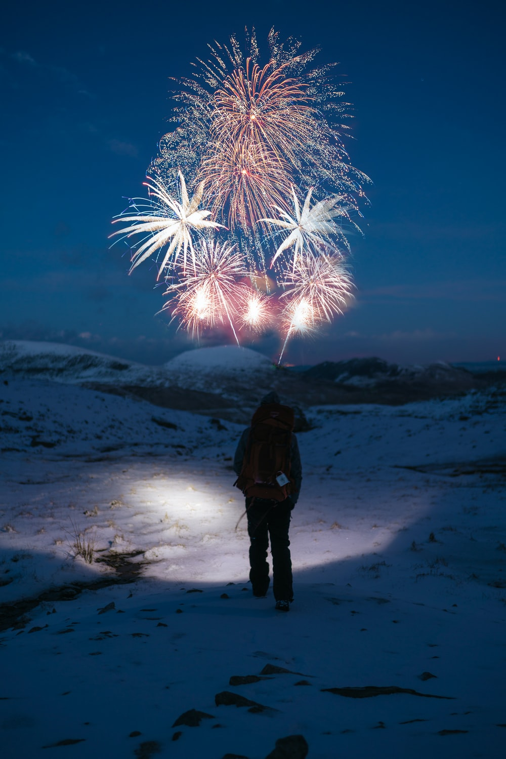 silhouette of person facing fireworks at nightime