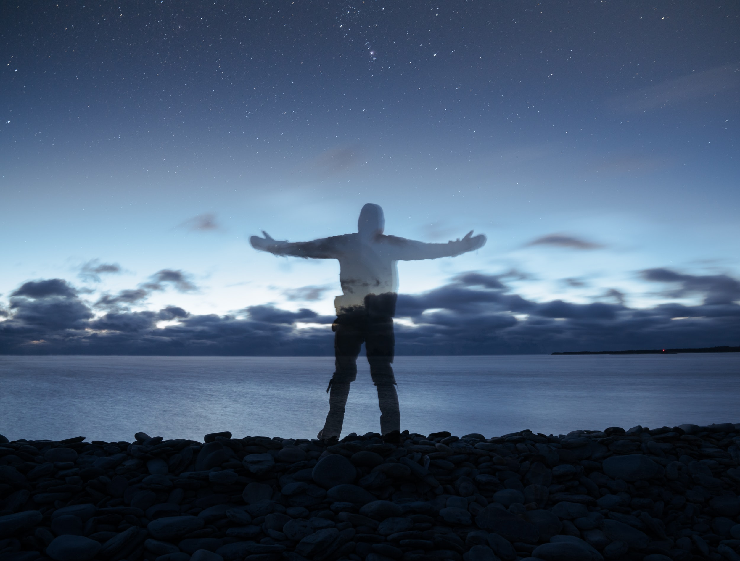 edited photo of person standing on rocks near sea during nighttime