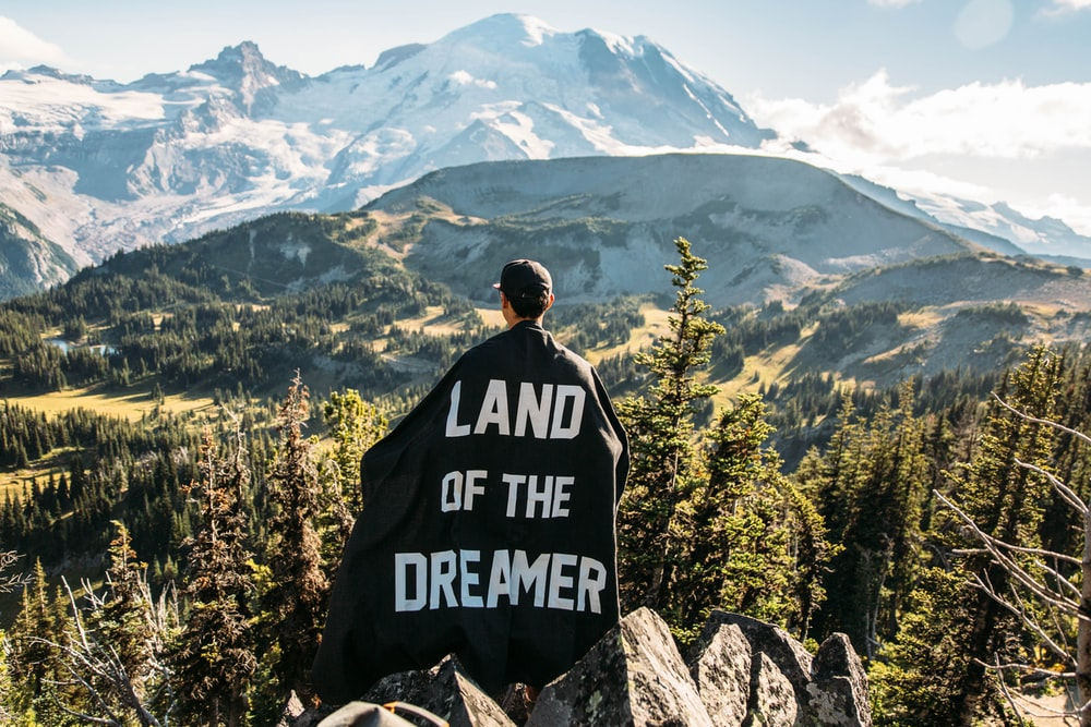 person standing on mountain peak with black land of the dreamer-printed cape on his back